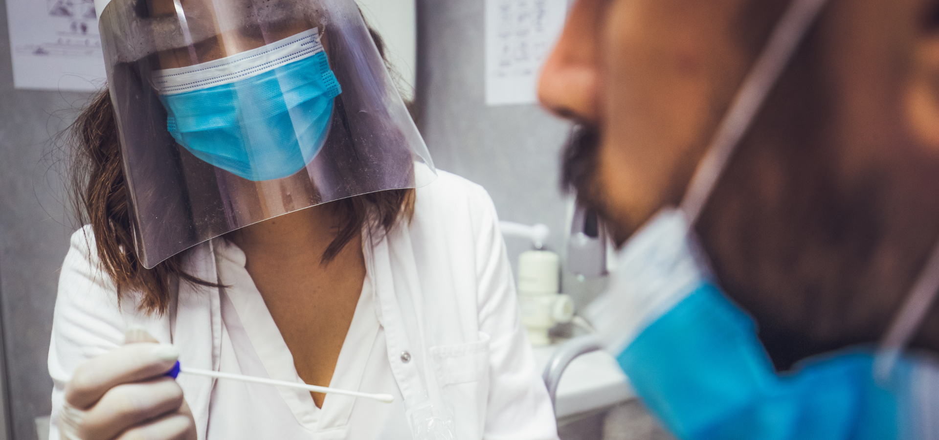 A nurse holds a swab as she approaches a man for a COVID19 test.