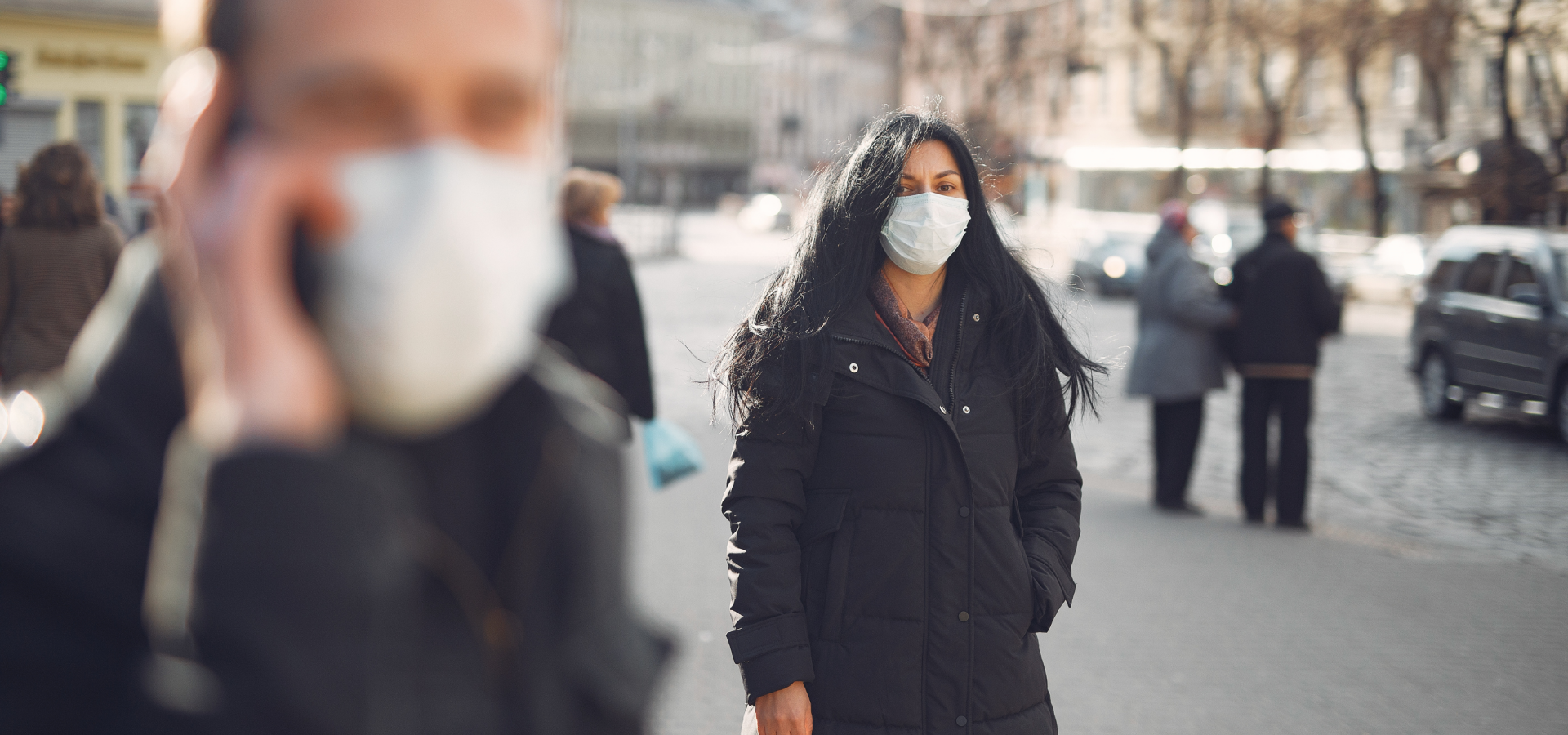 A woman walks down a city sidewalk wearing a face mask and a black coat.