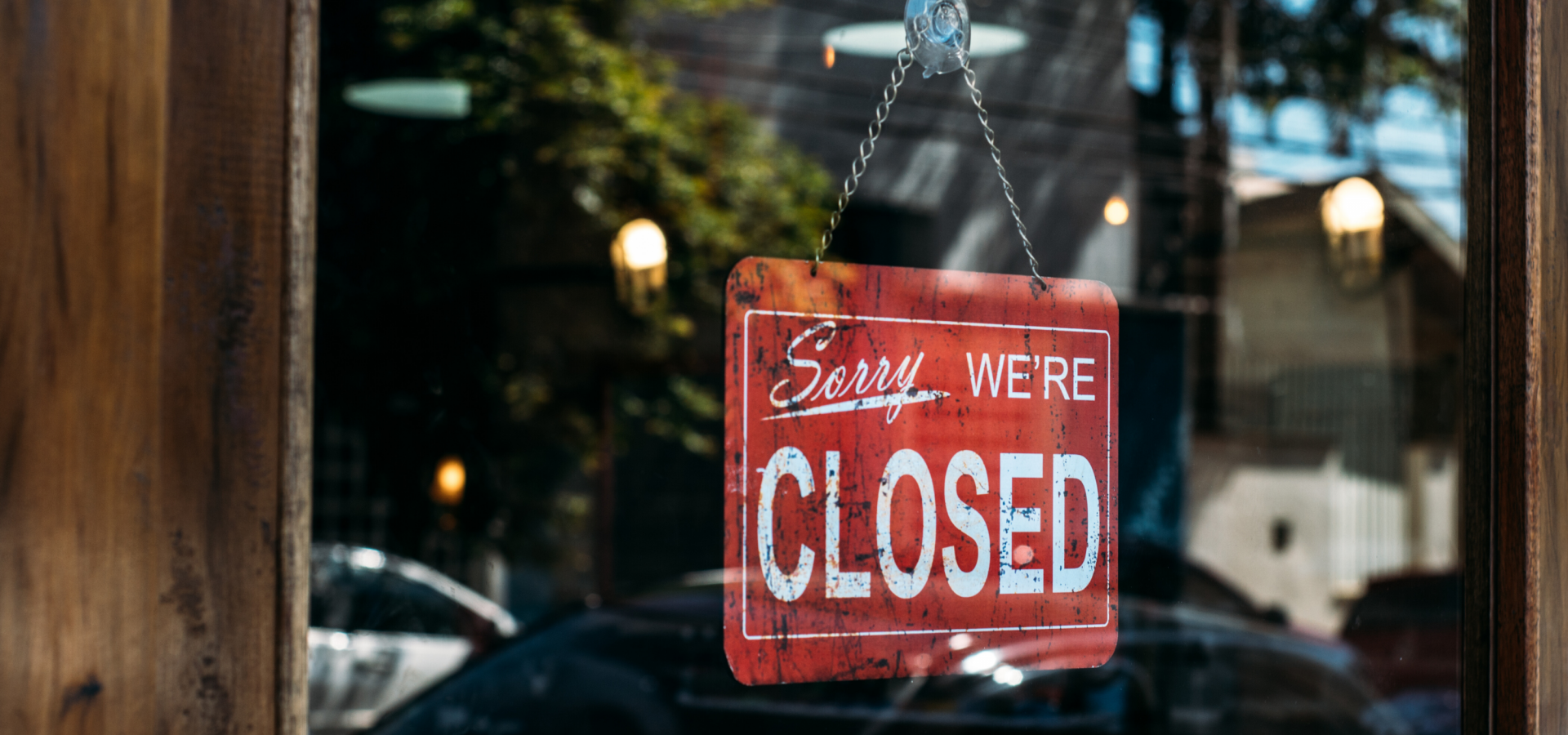 A red closed sign hangs in the glass door of a business.